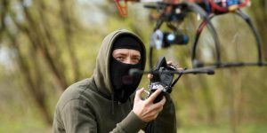Hooded Man Launching a Drone