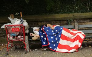Homeless Person sleeping under a Union Flag on a bench